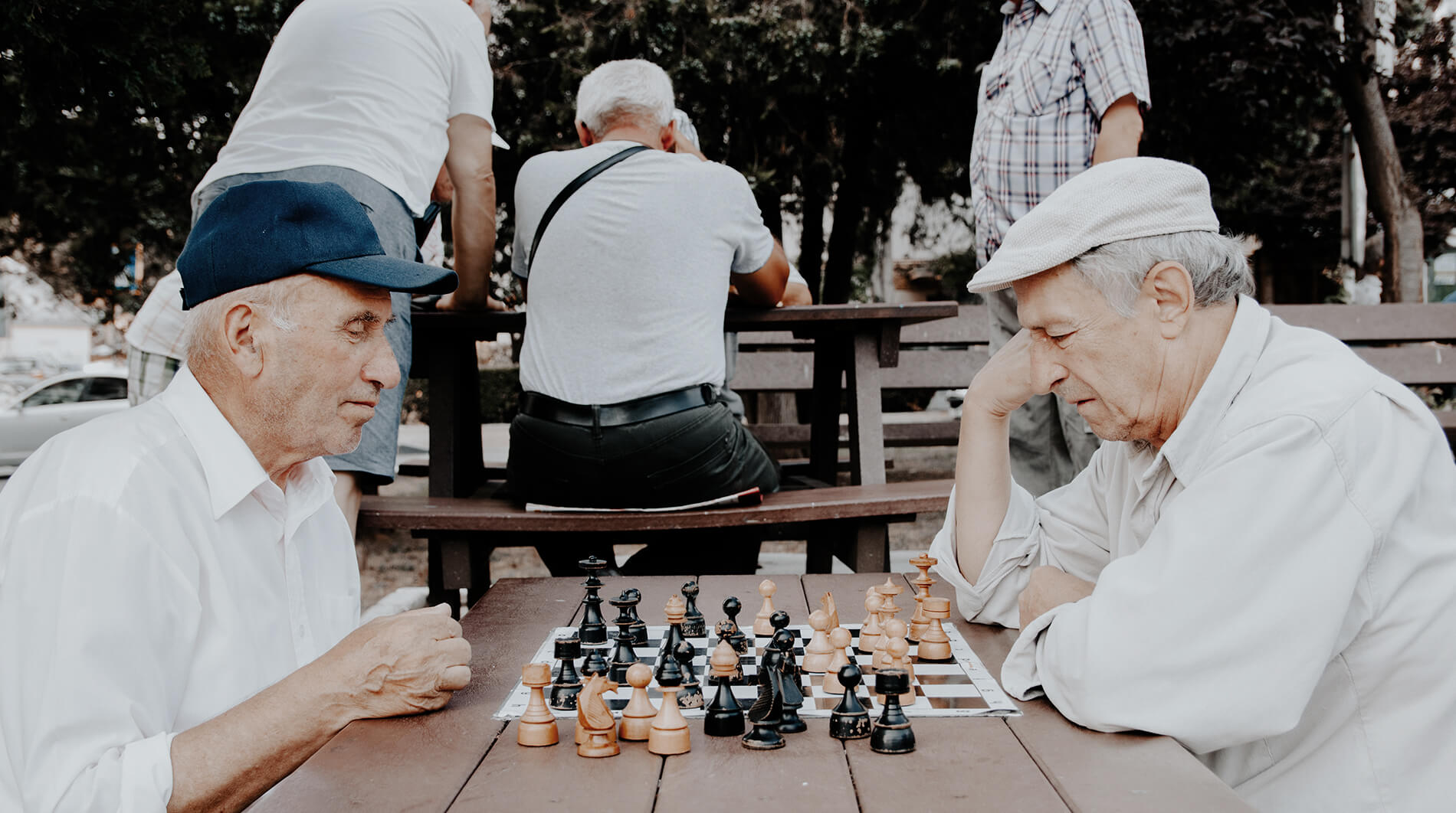Two senior citizens playing chess in the park