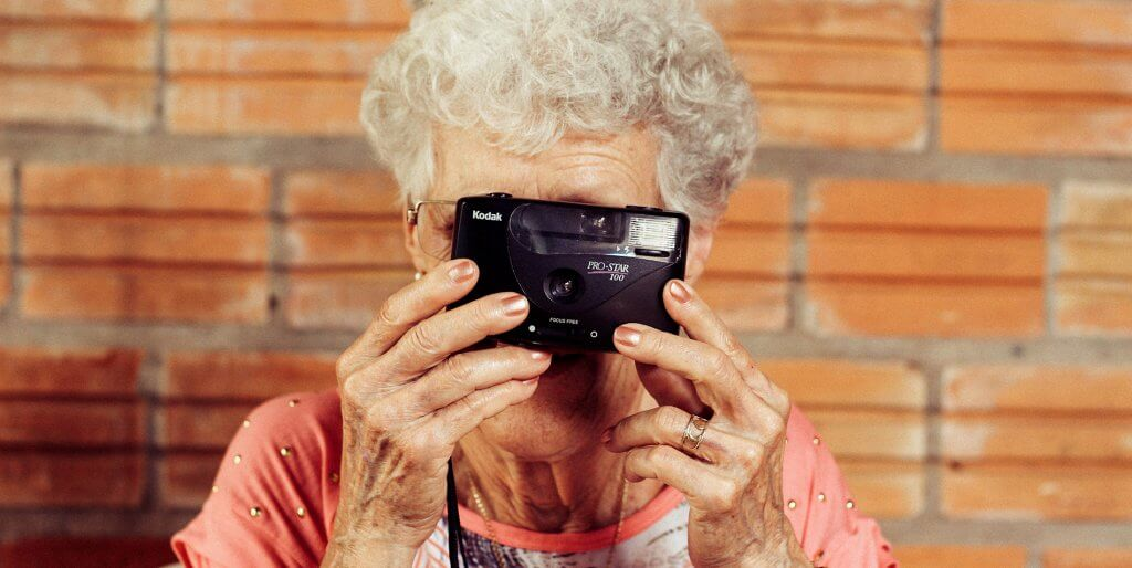 Senior lady taking a picture with an old camera