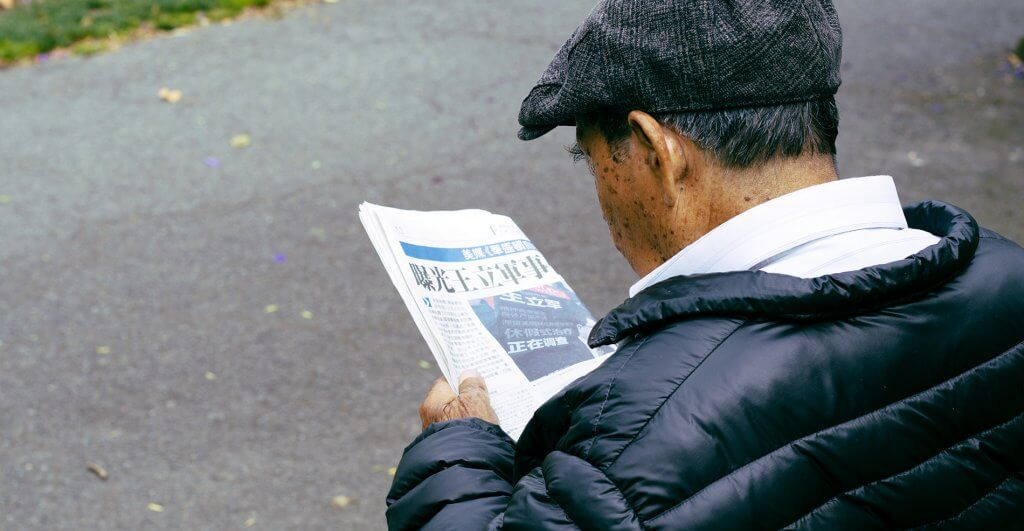 Old man reading the newspaper in the local park